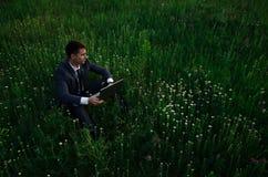 Buisnessman z laptopem siedzi na trawie obraz stock