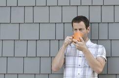 Buiten drinkend koffie voor een grijze achtergrond Royalty-vrije Stock Foto