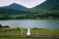 Buiten hangt de huwelijks bruids kleding De mening van het meer Landschap royalty-vrije stock foto