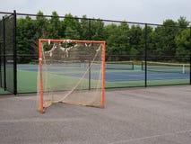 Buiten het seizoen, sla omhoog, de geroeste, haveloze zitting van het lacrossedoel op asfalthof met tearing netten stock afbeelding