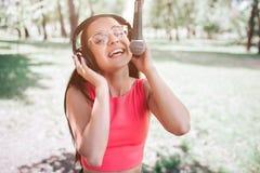 Buiten portret die van meisje en aan mic zingen bevinden zich Zij luistert tegelijkertijd aan muziek terwijl zij is Royalty-vrije Stock Afbeeldingen