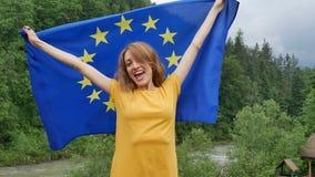 Buiten vrouwelijk portret van jong patriottisch meisje in de gele toevallige vlag van de kledingsholding van de Europese Unie ove stock video