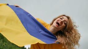 Buiten vrouwelijk portret van jong patriottisch meisje die blauwe en gele Oekraïense vlag over de hemelachtergrond houden stock videobeelden