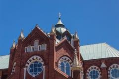 Buitendetails van een rode baksteen en een witte Gotische Heroplevingskerk, wolkenloze blauwe hemel stock afbeelding