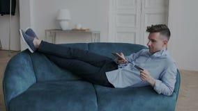 Buitengewone en knappe mens die op de bank in schoeisel in comfortabele positie thuis flats liggen Hij maakt online stock videobeelden