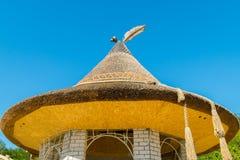 Buitengewoon ontwerp van een gazebo met een rietdak en elementen van smeedstuk in de vorm van een charmante bonnet stock foto