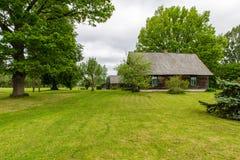 Buitenhuis met eiken bomen Stock Foto