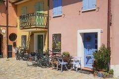 Buitenkant van de oude die woningbouw met fietsen bij de ingangen in Rimini, Italië worden geparkeerd Stock Fotografie