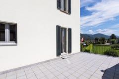 Buitenkant van een modern wit huis met een groot terras stock afbeelding