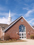 Buitenkant van een moderne rode baksteenkerk en een torenspits Royalty-vrije Stock Foto's