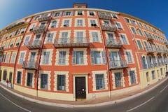 Buitenkant van het mooie rode gipspleisterhuis met traditionele Franse blindvensters en balkons in Nice, Frankrijk Stock Afbeeldingen