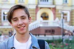 Buitenportret van tienerjongen Knappe tiener dragende rugzak bij één schouder en het glimlachen Royalty-vrije Stock Fotografie