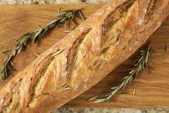 Buitensporig brood met kruiden en een knipselraad op een granietteller Stock Foto's