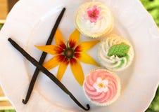 Buitensporige cakes met vanillestokken en bloem op wit royalty-vrije stock afbeelding
