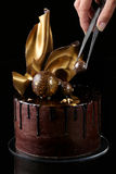 Buitensporige chocoladecake, zwarte achtergrond De hand van Th Royalty-vrije Stock Afbeeldingen