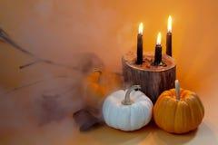 Buitensporige Halloween-pompoenen geplaatst ontwerp met zwarte kaarsen op sinaasappel stock fotografie