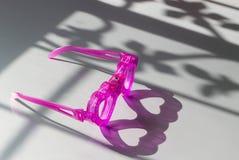 Buitensporige hart gestalte gegeven glazen op de vloer en licht van windo stock foto's