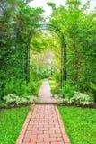 Bujny zieleni ogród z dokonanego żelaza altaną obraz royalty free