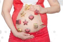 Buk av gravida kvinnan med julpynt Arkivfoton