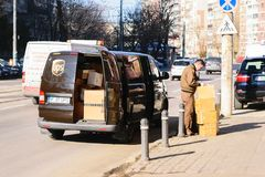 Bukarest, Rumänien - 25. Januar 2018: UPS-Arbeitskraft, die Pakete liefert UPS-Packwagen füllte mit bereitem, gelieferte Pakete z Lizenzfreies Stockbild
