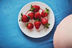 Buken av ett gravid kvinnasammanträde på en säng med ett blått ark och en platta av jordgubbar äta sunt havandeskap Str Royaltyfria Bilder