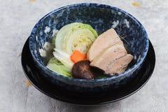 Buken för griskött för tryckspisen Kakuni med kål, japansk salladslök, shiitaken, morot tjänade som i blå keramisk bunke på washi Arkivbilder