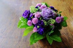 Bukett av blommor i en keramisk vas på en trätabell arkivfoto