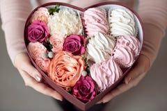 Bukett av blommor och marshmallower i en gåvaask av hjärta i kvinnliga händer Lyckönsknings- begrepp, försäljning Närbild royaltyfria foton