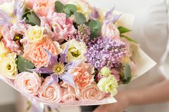 Bukett av delikat pastellfärgad färg härlig lyxig grupp av blandade blommor i kvinnas hand arbetet av blomsterhandlaren på a royaltyfri fotografi