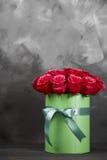 Bukett av delikata röda rosor i grön gåvaask på mörk grå lantlig bakgrund Hem- dekor Royaltyfri Bild