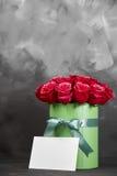 Bukett av delikata röda rosor i grön gåvaask på mörk grå lantlig bakgrund Hem- dekor Royaltyfria Bilder