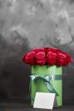 Bukett av delikata röda rosor i grön gåvaask på mörk grå lantlig bakgrund Hem- dekor Arkivfoto
