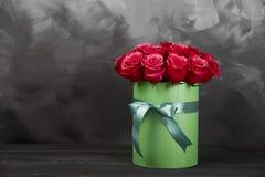 Bukett av delikata röda rosor i grön gåvaask på mörk grå lantlig bakgrund Hem- dekor Arkivfoton