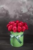 Bukett av delikata röda rosor i grön gåvaask på mörk grå lantlig bakgrund Hem- dekor Royaltyfri Foto