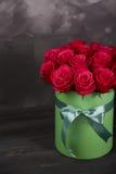 Bukett av delikata röda rosor i grön gåvaask på mörk grå lantlig bakgrund Hem- dekor Royaltyfria Foton