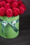 Bukett av delikata röda rosor i grön gåvaask på mörk grå lantlig bakgrund Hem- dekor Royaltyfri Fotografi