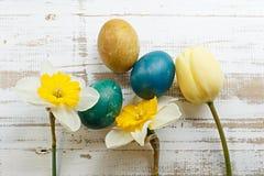 Bukett av den gula vårtulpan, påskliljor och handgjorda färgrika målade easter ägg mot lantlig träbakgrund Arkivbild