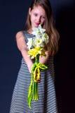 Bukett av gula och vita påskliljor i händerna av flickorna Royaltyfri Bild