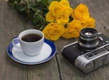 Bukett av gula rosor, koppen kaffe och ett retro kameran på en tabell Arkivbilder
