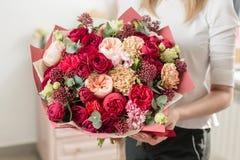 Bukett av högt rött färgat härlig lyxig grupp av blandade blommor i kvinnas hand arbetet av blomsterhandlaren på a arkivbilder