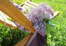Bukett av lilan som ligger på skrivbordstol Fotografering för Bildbyråer
