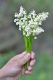 Bukett av liljekonvaljer i en kvinnlig hand Royaltyfri Fotografi