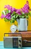 Bukett av lilor i emaljerad kokkärl på den antika resväskan, tappningradio, ringklocka på gul bakgrund Retro stilstilleben royaltyfri bild