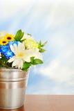 Bukett av ljusa blommor i en metallhink på träyttersida Fotografering för Bildbyråer