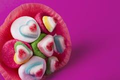 Bukett av marmelad och sötsaker i rosa förpacka på en rosa bakgrund arkivfoto