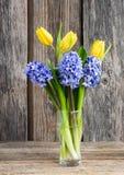 Bukett av nya gula tulpan och lila hyacinter på träbakgrund Arkivfoto
