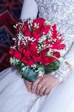Bukett av nya röda rosor i händer av bruden i en vit klänning Royaltyfri Foto