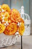 Bukett av orange rosor i en vit vide- korg och tappning bir Arkivbild