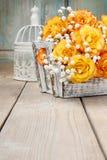 Bukett av orange rosor i en vit vide- korg och tappning bir Royaltyfri Foto