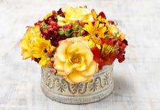 Bukett av orange rosor och höstväxter i keramisk vas för tappning Royaltyfri Fotografi